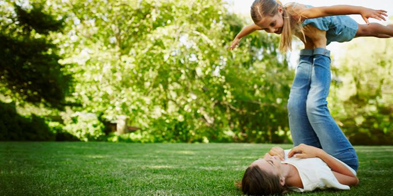 Mother and daughter playing outside in Maine. The yard is green and healthy. They use The Turf Doctor for lawn care in Maine.
