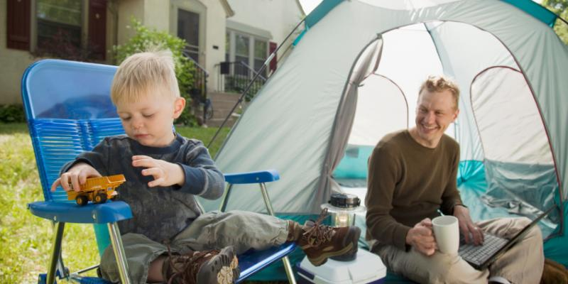 A toddler and his father camping in the front yard of their home. The Turf Doctor provides mosquito control in Maine so families can spend time outside without the hassle of mosquito bites.